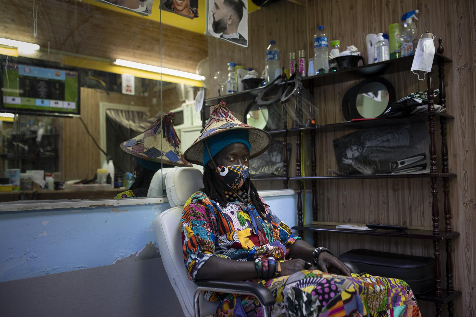 """Alpha (26) es senegalés, llegó a España hace dos años y aún no tiene papeles. Trabaja con su tío en la peluquería que éste regenta en Lavapiés. Desde que han vuelto a abrir, la sonrisa ha vuelto a su cara, aunque no podamos verla debajo de la mascarilla. """"Lo pasé mal durante el confinamiento, pero sabía que era por la salud de la gente"""", recuerda. Su familia está bien, todos, el Covid-19 no ha golpeado en Senegal tan fuerte como en Europa. """"Yo sigo mi destino"""", dice, una expresión muy africana que significa que aceptan lo que venga sin miedo. También la """"nueva normalidad"""", que afronta con sus vistosos trajes africanos que cose él mismo, porque no quiere perder sus raíces, eso sí, """"al estilo moderno"""""""