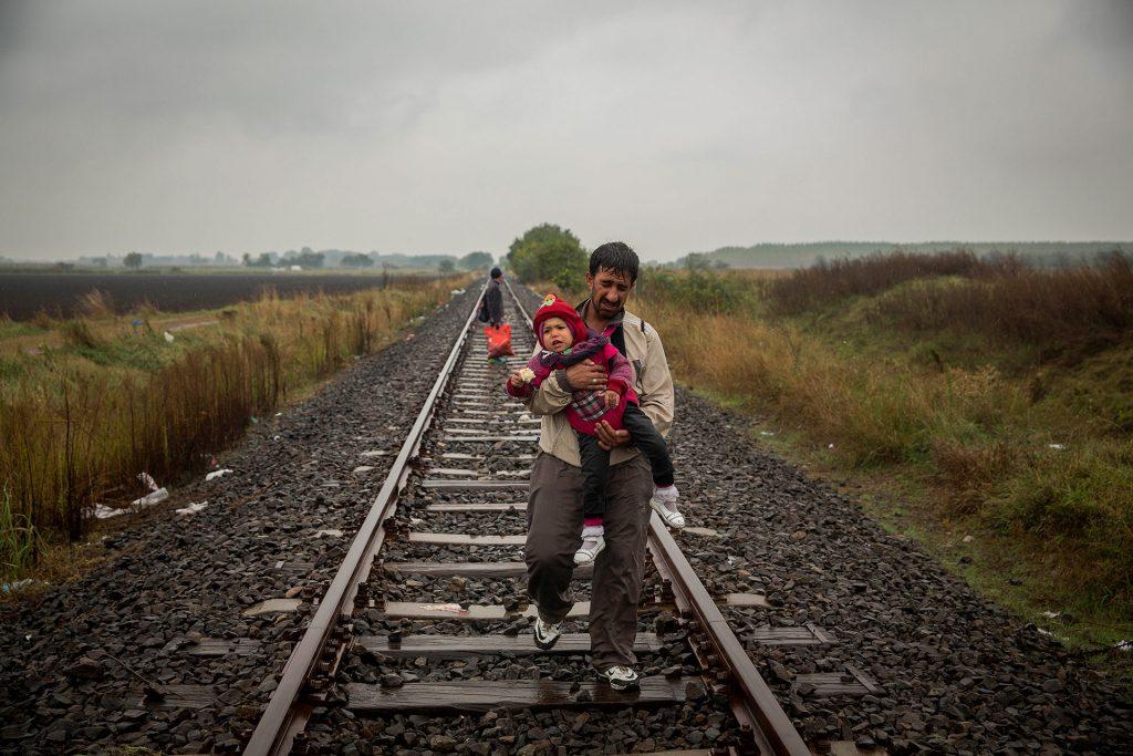 Un padre camina por las vías del tren llevando a su hijo en brazos unos cientos de metros después de haber cruzado la frontera entre Serbia y Hungría entrando en la localidad de Roszke. (Roszke. Hungría. 10/09/2015).