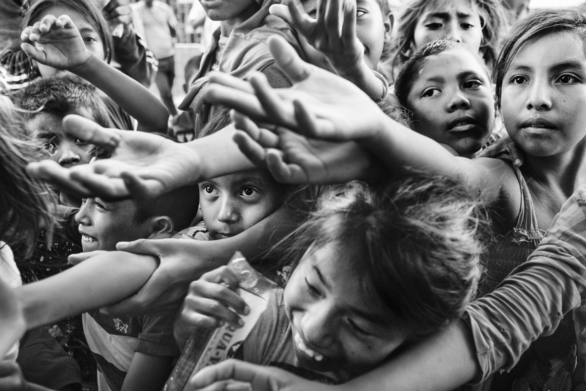Children crowd at the door of a UNHCR attention center to receive donated water at the border town of Paraguachón, Colombia. Charity organizations and NGOs help supply people with medical attention, water, and food. However, the magnitude of the migration is bigger than the international agencies' capability to respond to it. Many end up in informal settlements or living on the streets.