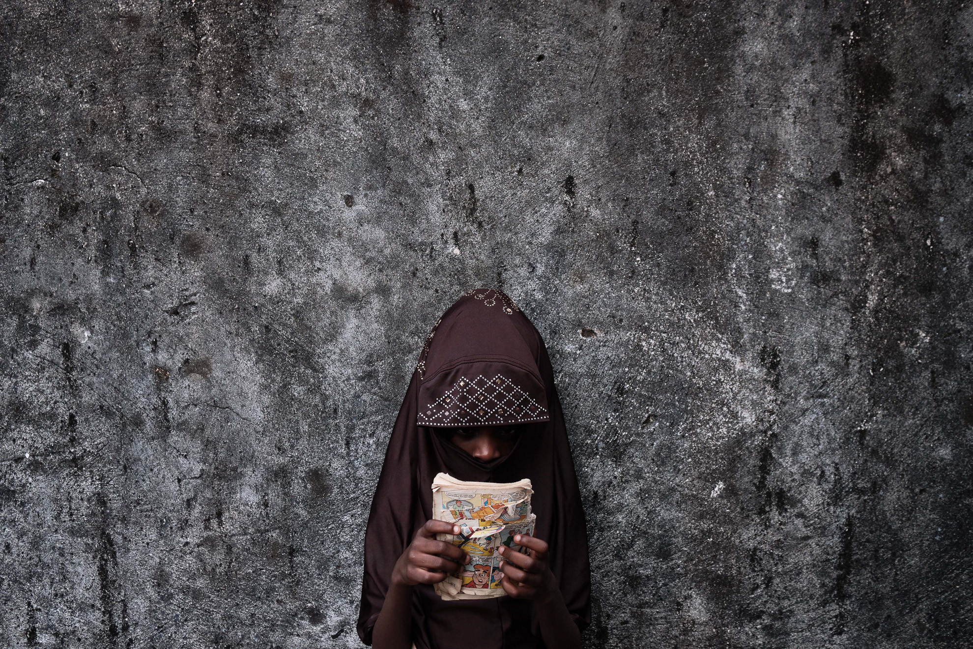 Fatimah is 6 years old, born in Boko Haram captivity to a mother who died during a raid. She spents time at her extended family home in Borno North East Nigeria, scanning pictures of a comic book 'Archie', hoping that one day she will go to school.