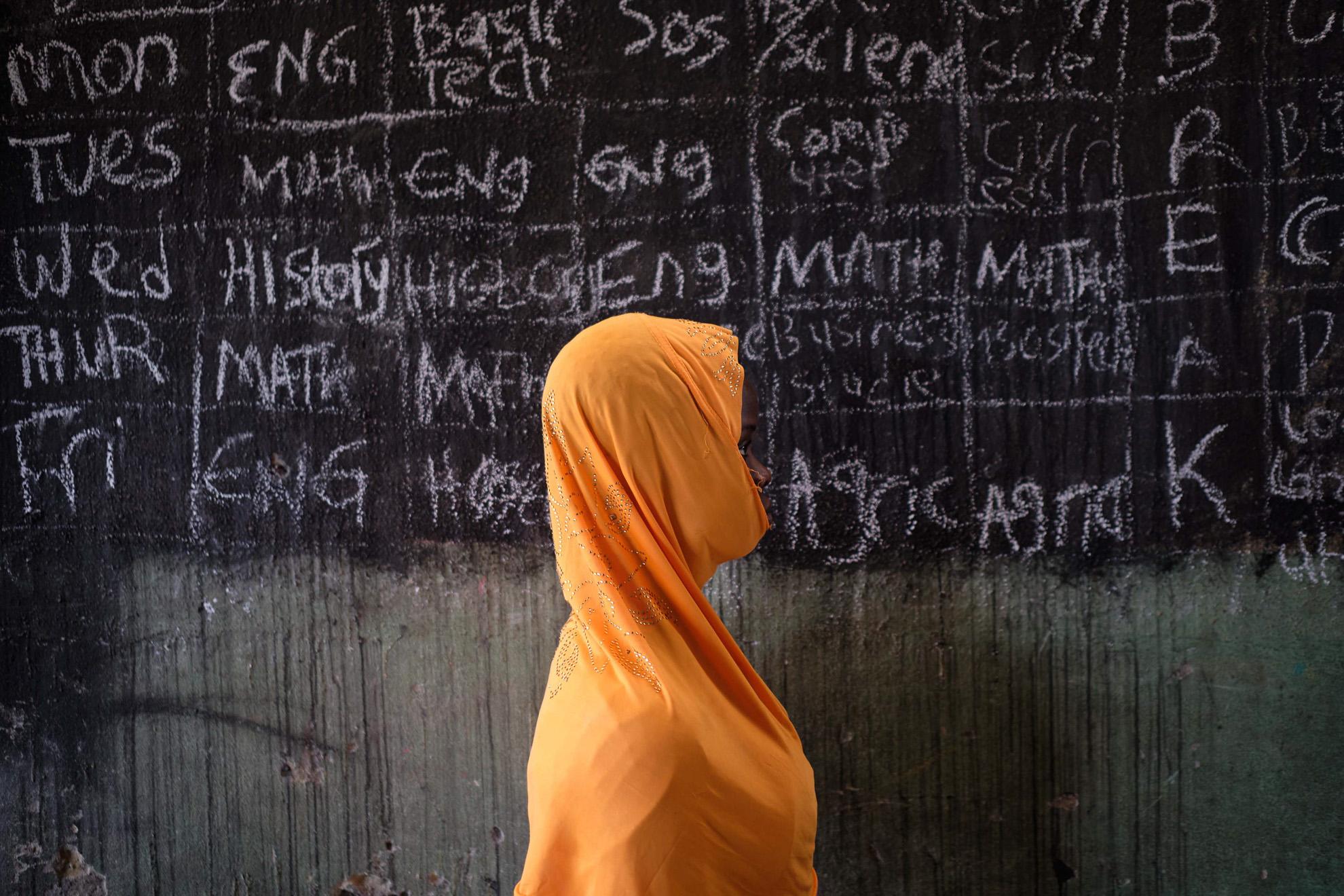 Ladi (nombre ficticio) tiene 16 años, nació en el noreste de Nigeria. Fue secuestrada por su tío, un simpatizante de Boko Haram. Se casó dos veces con dos combatientes de grupos terroristas que murieron en diferentes ataques a bases militares. Sin su marido para protegerla, fue atada con una bomba para detonar en una iglesia. Ella sobrevivió y pasa tiempo coleccionando bolígrafos, ya que cree que el bolígrafo es más poderoso que la espada. Quiere convertirse en escritora. Vive en Biu.