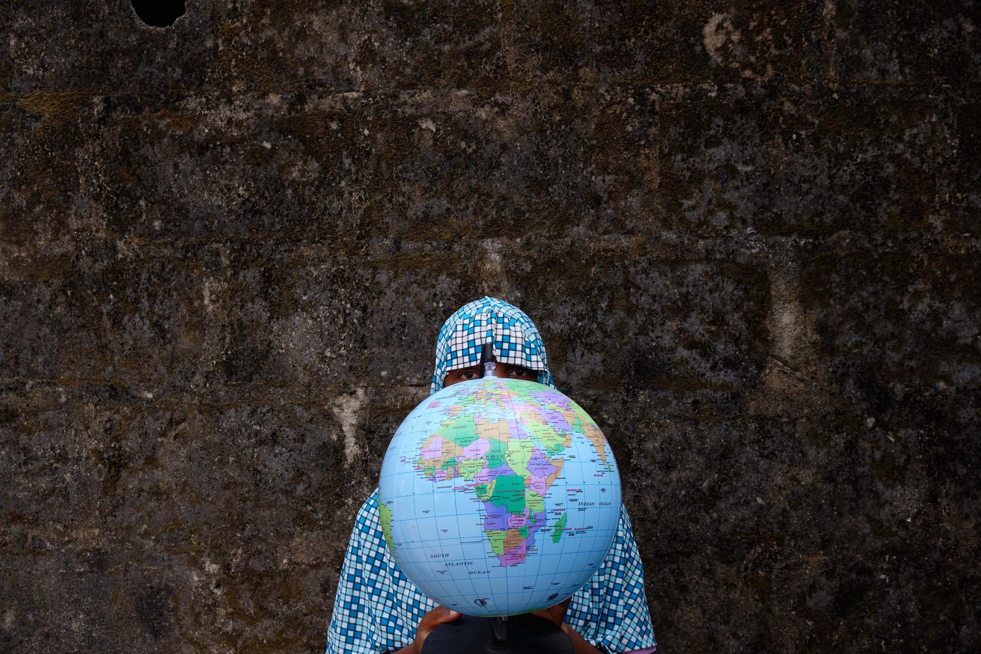 Hassana (nombre ficticio) 16 años de edad, en su escuela en Izghe, al noreste de Nigeria. Fue secuestrada por Boko Haram con su hermana gemela que murió en el campamento terrorista. Regresó a su casa y se encontró con que su aldea había sido devastada y sus padres habían sido asesinados por Boko Haram. Le encanta estudiar el mapa mundial, espera poder viajar por el mundo algún día, porque cree que es parte de la educación.