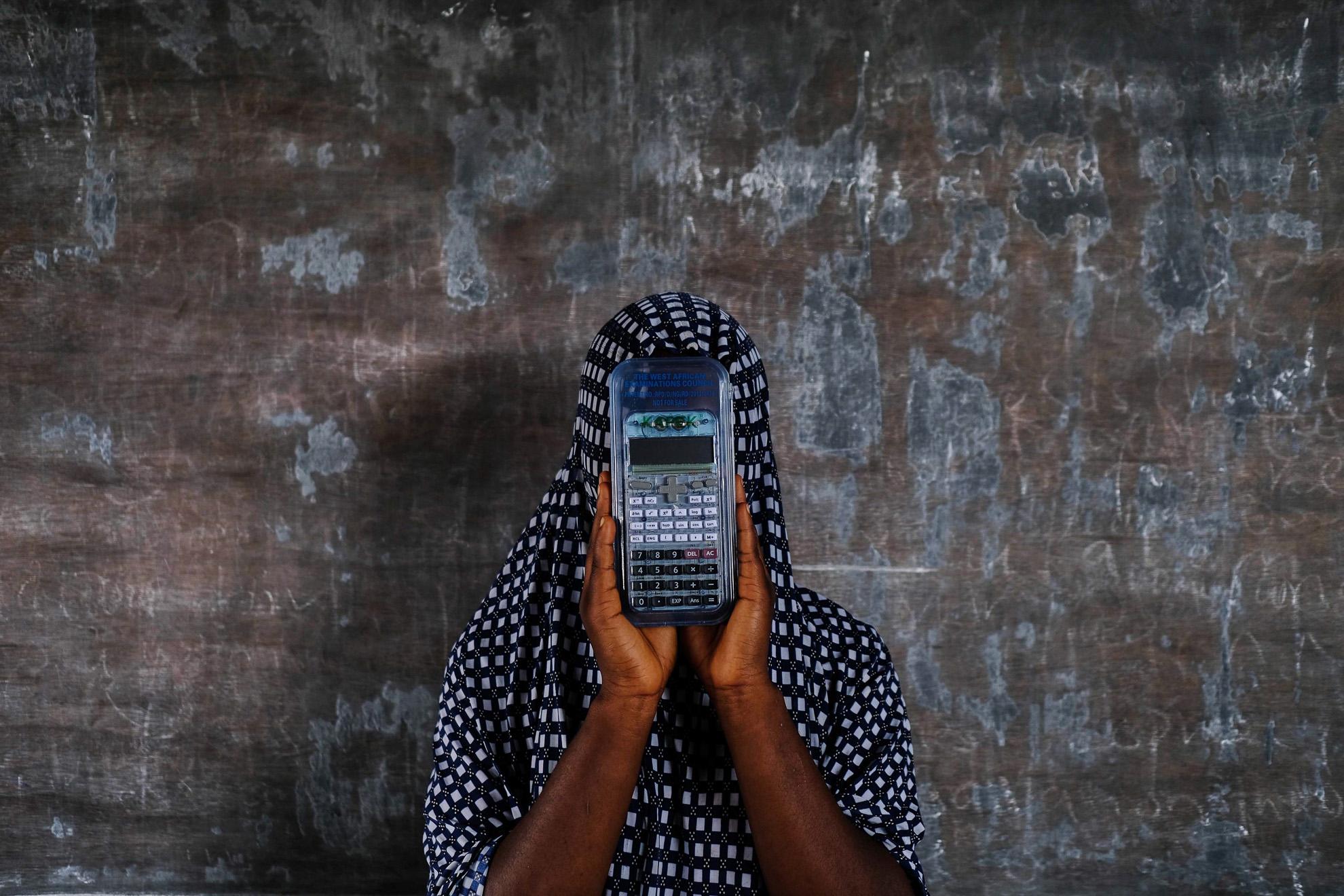 Zahrah (nombre ficticio) 17 años de edad, en su escuela en Chibok, al noreste de Nigeria. Fue secuestrada por Boko Haram cuando tenía 15 años. El grupo terrorista la capturó de camino a la escuela. Se negó a detonar una bomba que el grupo terrorista le ató a su pecho. Asiste a una lección organizada por un maestro jubilado en su pueblo asolado por Boko Haram. Quiere ser contable.