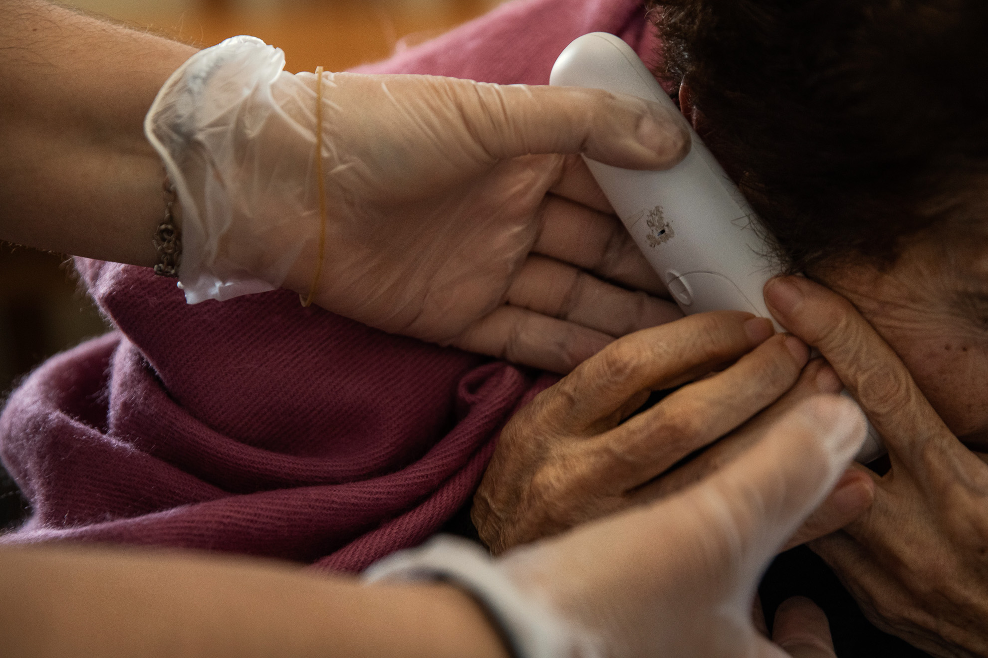 A worker holds the phone so that an elderly woman can speak with her daughter, at a nursing home, province of Barcelona, Spain, April 18, 2020.