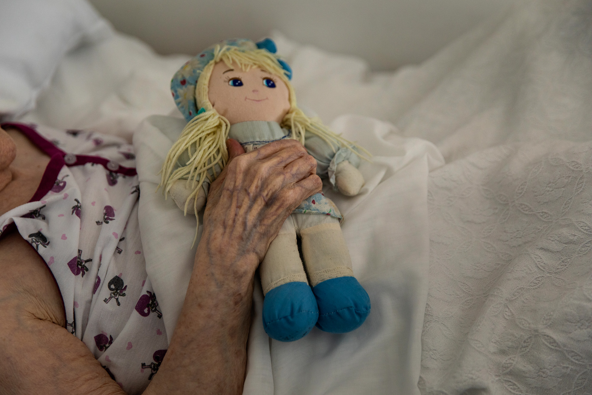 An elderly woman holds a doll in the room of the residence where she remains confined due to the pandemic, province of Barcelona, ​​Spain, April 26, 2020.