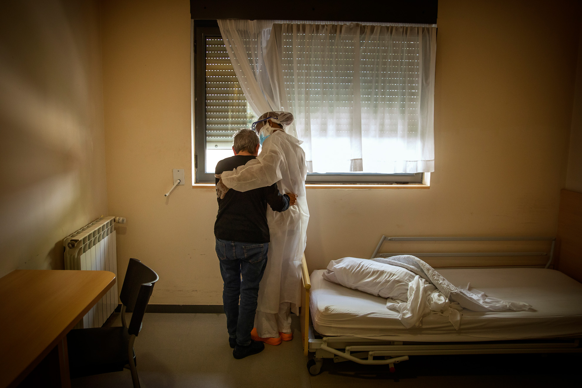 An elderly woman and a worker embrace each other in the room in which the woman remains confined due to the pandemic, at a nursing home, province of Barcelona, ​​Spain, April 29, 2020.