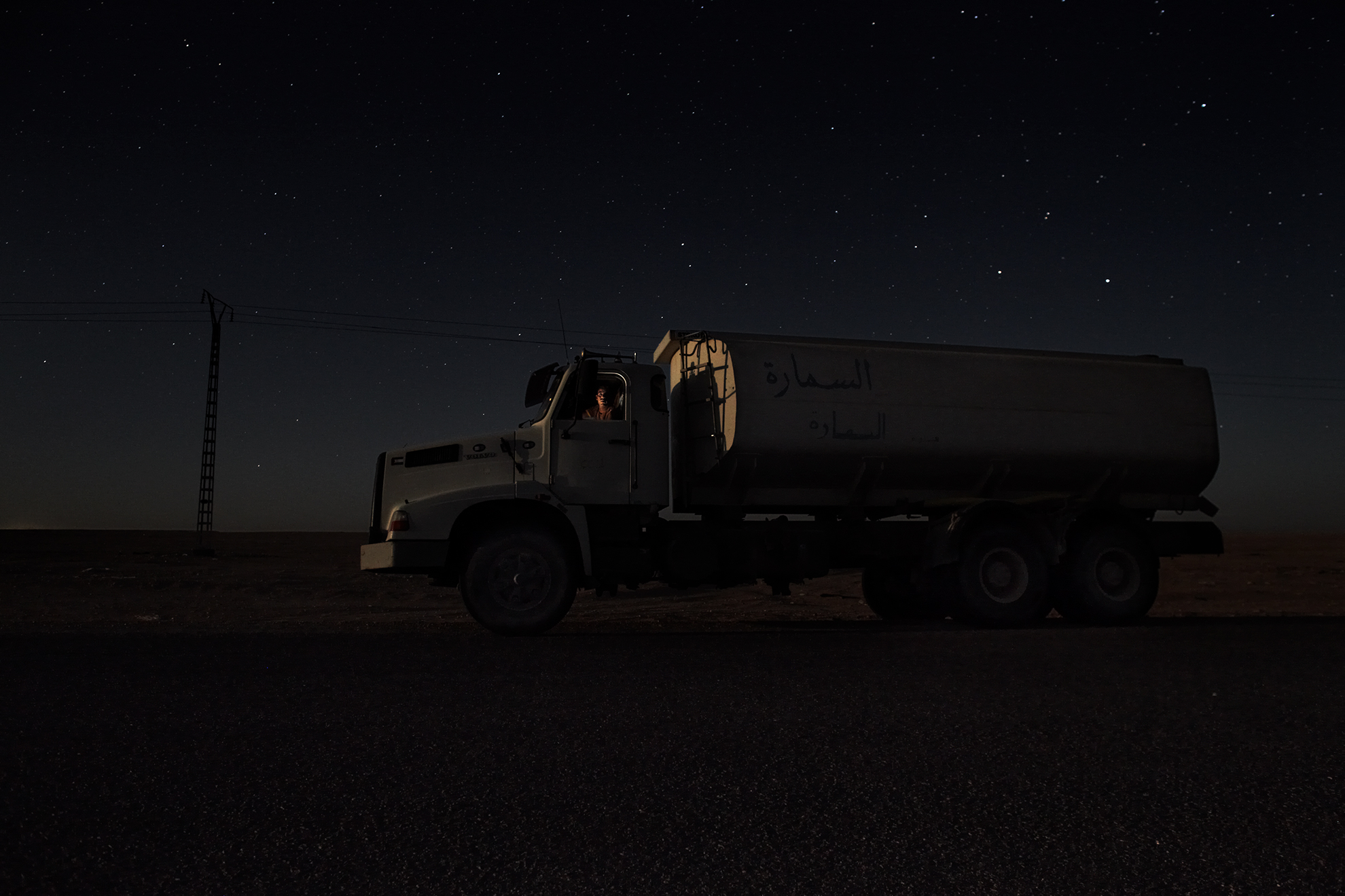 Abdullah Kheylanie, de 30 años, conductor de un camión de agua, fotografiado en la carretera a las afueras del campamento de refugiados de Smara (Argelia).