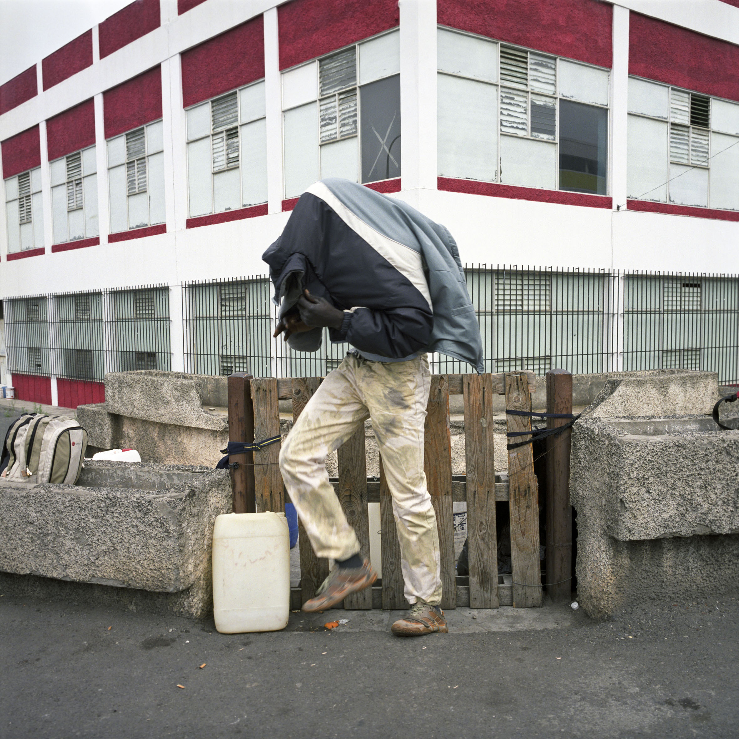 Inmigrante indocumentado de Malí se esconde. Junto con otros compatriotas, lavan un coche por 10 €. Una vez en Europa, los inmigrantes indocumentados corren más riesgo de ser explotados, de trabajar muchas horas, de vivir en alojamientos precarios y de tener mala salud.