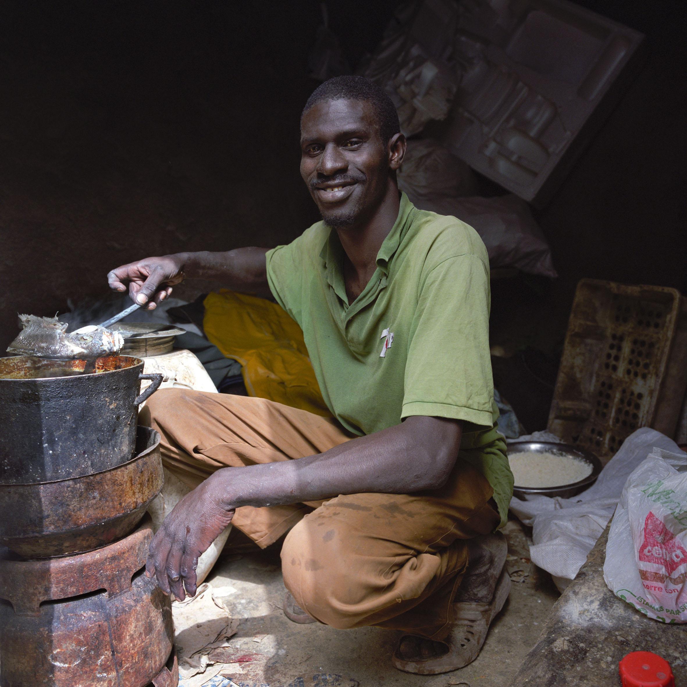 Un inmigrante de Senegal cocina comida en su refugio improvisado en Nuakchot. Mauritania es una de las diferentes rutas utilizadas por los inmigrantes indocumentados en su intento de llegar a Europa. Viviendo en condiciones precarias de salud y en alojamientos inseguros, los emigrantes sufren grandes choques y traumas en los países de acogida, hecho que tiende a vulnerar aún más su salud psicológica.